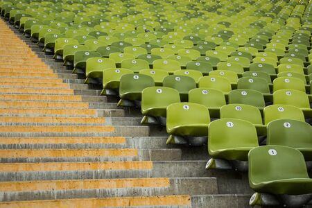 Rows of green seats and stairs in stadium