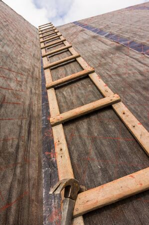 Roofer ladder on roof with roofing felt and markings authentic