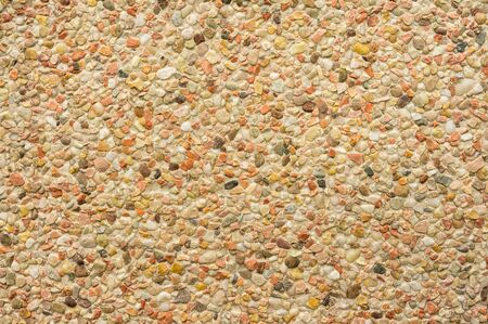 Background product sample closeup of an exposed aggregate concrete slab with pebbles light colors