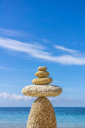 Esotericism meditation balance pebble in front of a blue sky
