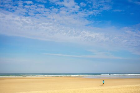Landscape running jogger on wide sandy beach in summer Foto de archivo