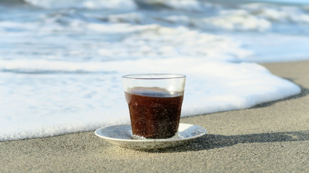 a glass of coffee on the sand and waves