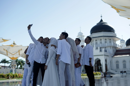 Banda Aceh, Aceh Province  Indonesia - June 3 2018 :Tourists are taking picturesselfie in front of Baiturrahman grand mosque in Banda Aceh, Indonesia. Editorial