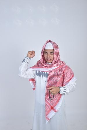 Muslim man holding prayer beads and praying