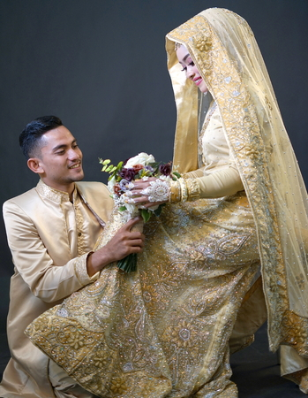 Bride and groom holding blooms, Indonesian wedding ceremony
