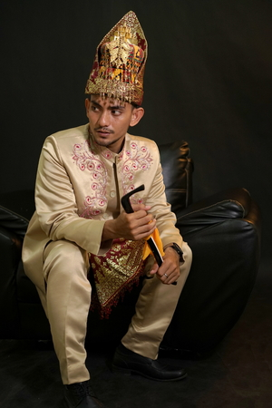 Handsome man in traditional acehnese dress holding Rencong (Traditional aceh weapon) 写真素材