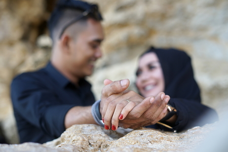 Muslim Couple holding hand in the mountains Rock with Black Dress