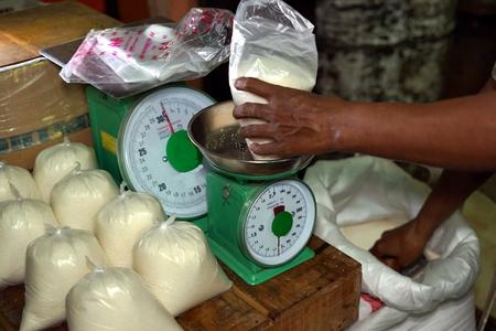 Vendor measuring sugar for sale