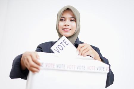Hijab girl putting a ballot into a Ballot box