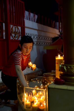 Banda Aceh, Indonesia - February 19, 2015: Chinese woman praying during Chinese New Year celebration at Dharma Bhakti Temple in Banda Aceh City