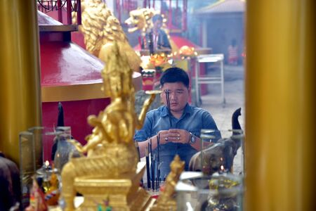 Banda Aceh, Indonesia - February 19, 2015: Chinese new year celebrations. Man praying in front of Golden Four Faced Buddha at Vihara Dharma Bhakti in Banda Aceh City