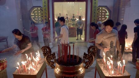Banda Aceh, Indonesia - February 19, 2015: During Imlek or Chinese New Year at Dharma Bhakti Temple, Chinese worshippers are praying and blessing with incense burners in Banda Aceh City.