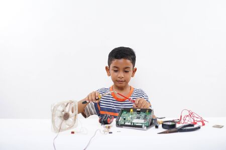 Asian schoolboy  electrician repairing computer part at home