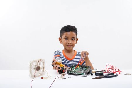 Asian schoolboy  electrician repairing computer part at home Stock Photo - 130626065