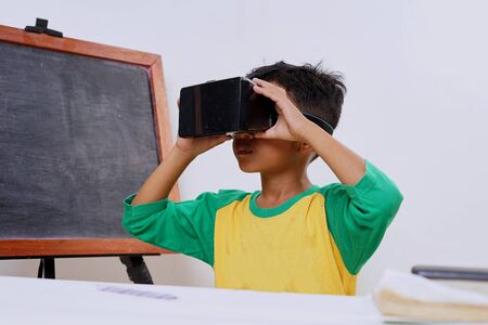 Excited kid using e learning with VR glasses