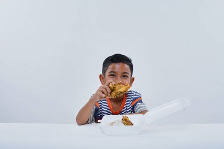 Schoolboy eating fried chicken fastfood on white background Stok Fotoğraf