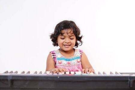 Happy little girl playing electric piano