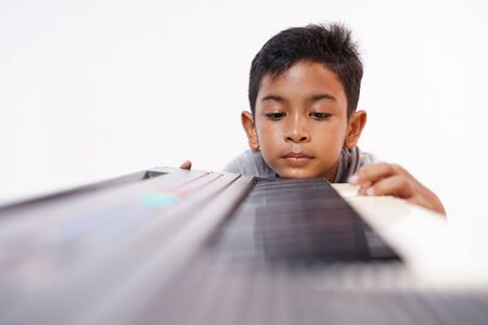 Asian little boy frustrated with playing piano