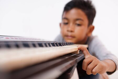 Asian little boy frustrated with playing piano 스톡 콘텐츠 - 131805785