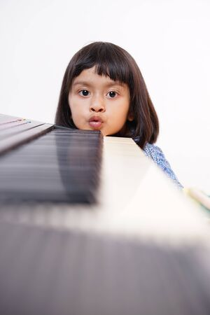 Happy little girl with electric piano
