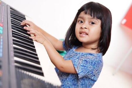 Smiling girl plays on the electric piano