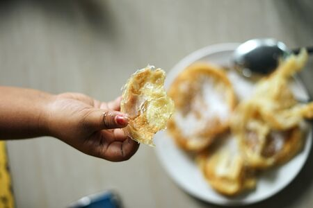 Child hand holding Roti Canai or chapati at traditional street food market