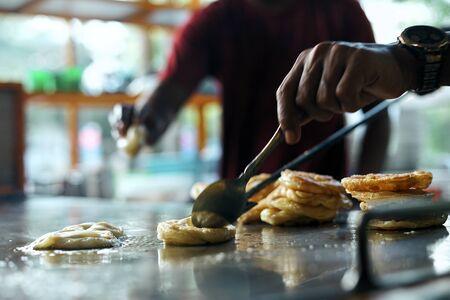 Street food vendor stirring Martabak Aceh in big pan
