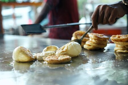 Street food vendor stirring Martabak Aceh in big pan
