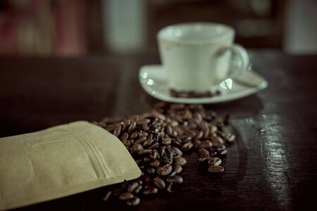 Glass of Black Coffee and roasted coffee beans on the wooden Table