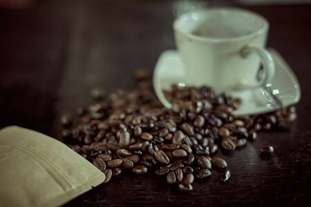 Grinded Arabica coffee beans with vintage wooden background