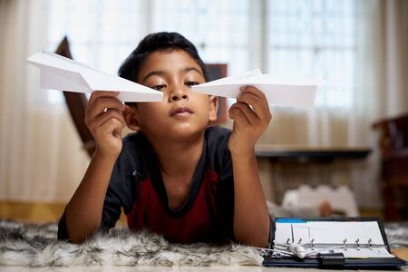Young schoolboy playing with a white paper plane