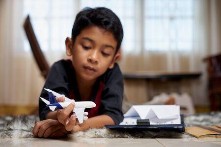Ragazzo sdraiato in una stanza da bagno che gioca con aeroplani giocattolo