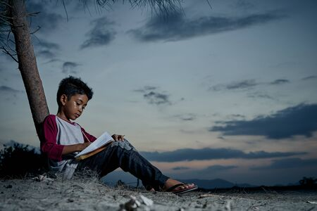 Schoolboy doing homework outdoor under the sky at night
