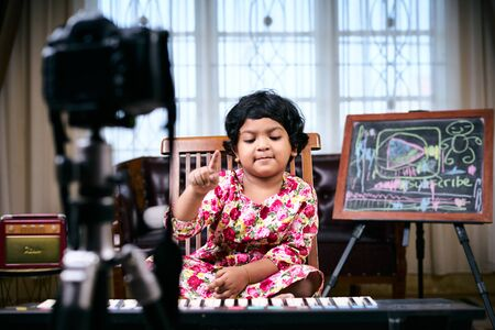 Happy Little girl making video tutorial how to play piano Imagens