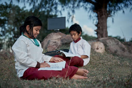 Two happy elementary students with a book and computer studying at natural park, New Normal Education concept