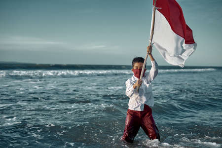 Schoolboy holding Red and White Flag at the Beach, commemorate Indonesia's independence day