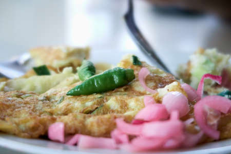 Spicy Egg Omelet on a white plate with Chilli and slice Onion