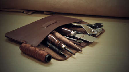 Leather craft tools on a wooden table at traditional workshop