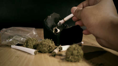Closeup Hand holding a marijuana joint on the table
