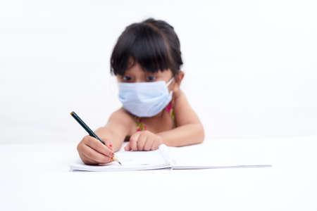 Close-up little girl hand writing in notebook, Wearing a protective face mask Zdjęcie Seryjne
