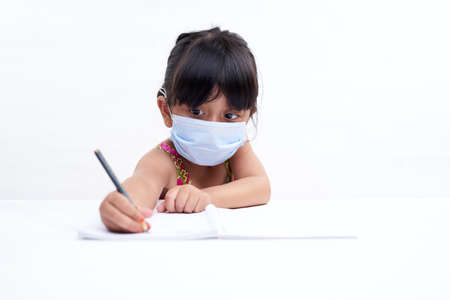 Cute little girl writing in notebook Wearing a protective face mask, Homeschooling New Normal education concept