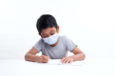 Schoolboy with a protective face mask writing in notebook at home, Homeschooling New Normal education concept