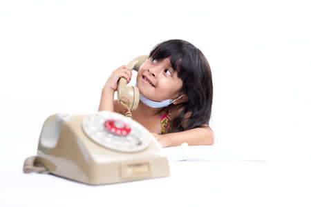 Young Asian toddler Talking on vintage telephone with cute expression