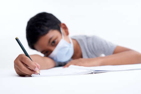 Schoolboy with protective face mask tired doing study and homework at home. new normal education concept