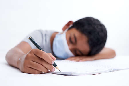 Little boy fell asleep while writing homework, new normal education concept