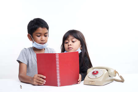 A brother and sister with protective face mask studying together at home, homeschooling new normal concept
