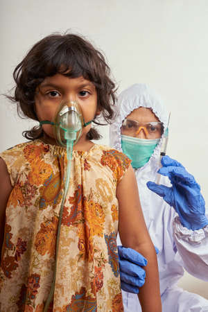 Virologist in protective suit makes vaccination to Little girl patient infected with Corona Virus Stockfoto - 160524233