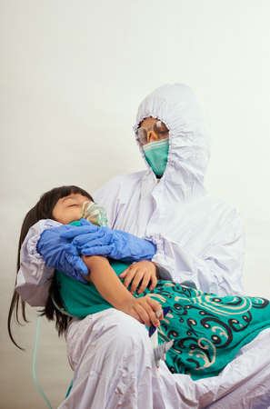 Pediatrician doctor wearing protective suit takes care of child patient , coronavirus protection concept