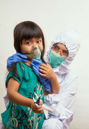 Nurse in protective suit takes care of the patient child in hospital Quarantine room Stockfoto