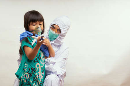 Nurse in protective suit takes care of the patient child in hospital Quarantine room Zdjęcie Seryjne
